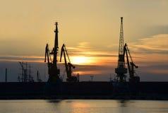 口岸在日落的货物起重机 库存照片