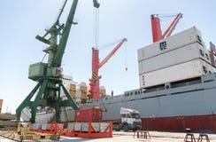 口岸起重机举的容器和装载的船有货物的 库存照片