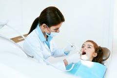 口腔医学 牙医与在牙齿诊所的女孩牙一起使用 库存图片