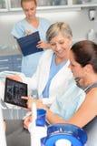 口腔外科牙医展示X-射线片剂的患者 库存图片