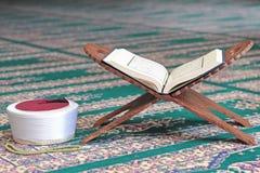 古兰经、阿訇菲斯和在一个木立场的念珠小珠在清真寺 免版税库存图片