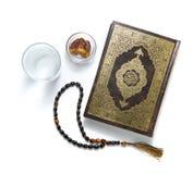 古兰经圣经、水、日期和念珠,隔绝在白色 免版税库存图片