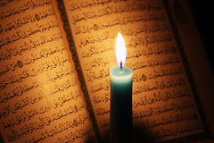 古兰经或古兰经圣经与蜡烛在烛光 免版税库存图片