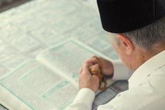 读古兰经的一个老人 库存图片
