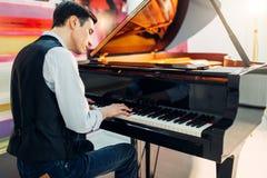 古典黑大平台钢琴的男性钢琴演奏家 免版税库存图片