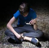 古巴人Treefrog Osteopilus septentrionalis 男孩发光手电和神色在青蛙,坐他的手 晚上 库存照片