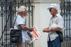 古巴哈瓦那 有古巴报纸的两个老人 免版税库存照片