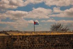 古巴的旗子反对天空的在堡垒墙壁 圣萨尔瓦多de la蓬塔老殖民地城堡  哈瓦那 古巴 图库摄影