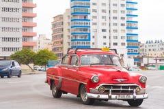 古巴,哈瓦那- 2017年5月5日:在城市街道上的红色美国减速火箭的汽车 复制文本的空间 免版税库存照片