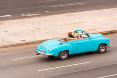 古巴,哈瓦那- 2017年5月5日:在城市街道上的美国天蓝色的减速火箭的敞蓬车 复制文本的空间 免版税库存照片