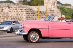 古巴,哈瓦那- 2017年5月5日:在城市街道上的美国桃红色减速火箭的敞蓬车 复制文本的空间 特写镜头 免版税库存图片