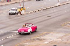 古巴,哈瓦那- 2017年5月5日:在城市街道上的美国桃红色减速火箭的敞蓬车 复制文本的空间 免版税库存照片