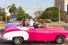 古巴,哈瓦那- 2017年5月5日:在城市街道上的美国桃红色减速火箭的敞蓬车 特写镜头 图库摄影