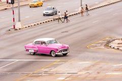 古巴,哈瓦那- 2017年5月5日:在城市街道上的美国桃红色减速火箭的汽车 复制文本的空间 免版税库存照片