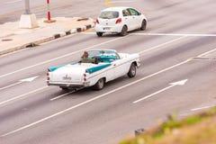 古巴,哈瓦那- 2017年5月5日:在城市街道上的美国白色减速火箭的敞蓬车 复制文本的空间 库存照片