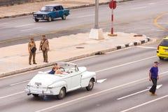 古巴,哈瓦那- 2017年5月5日:在城市街道上的美国白色减速火箭的敞蓬车 复制文本的空间 免版税库存图片
