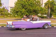 古巴,哈瓦那- 2017年5月5日:在城市街道上的美国紫色减速火箭的敞蓬车 复制文本的空间 免版税库存照片