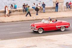 古巴,哈瓦那- 2017年5月5日:在城市街道上的美国红色减速火箭的敞蓬车 复制文本的空间 免版税库存照片