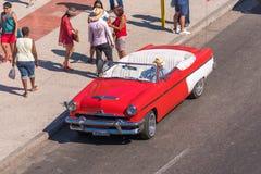 古巴,哈瓦那- 2017年5月5日:在城市街道上的美国红色减速火箭的敞蓬车 复制文本的空间 免版税库存图片
