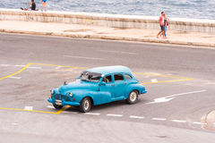 古巴,哈瓦那- 2017年5月5日:在江边的美国蓝色减速火箭的汽车 复制文本的空间 免版税库存图片