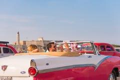 古巴,哈瓦那- 2017年5月5日:在灯塔背景的美国桃红色减速火箭敞蓬车 复制文本的空间 特写镜头 库存图片