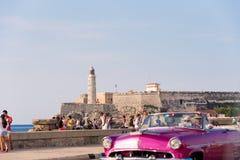 古巴,哈瓦那- 2017年5月5日:在灯塔背景的美国桃红色减速火箭敞蓬车 复制文本的空间 免版税图库摄影