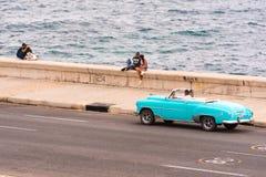 古巴,哈瓦那- 2017年5月5日:美国天蓝色的减速火箭的敞蓬车沿Malecon沿海岸区乘坐 复制文本的空间 库存图片