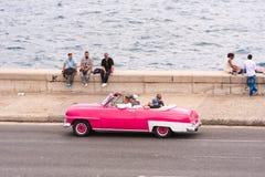 古巴,哈瓦那- 2017年5月5日:美国桃红色减速火箭的敞蓬车沿Malecon沿海岸区乘坐 复制文本的空间 免版税库存照片