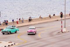 古巴,哈瓦那- 2017年5月5日:美国桃红色减速火箭的汽车沿Malecon江边乘坐 复制文本的空间 免版税库存照片