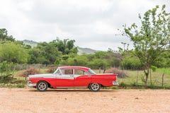 古巴,哈瓦那- 2017年5月5日:美国红色减速火箭的汽车在乡下 复制文本的空间 库存照片