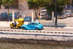 古巴,哈瓦那- 2017年5月5日:美国蓝色减速火箭的汽车沿江边乘坐 复制文本的空间 免版税图库摄影