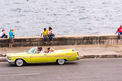 古巴,哈瓦那- 2017年5月5日:美国黄色减速火箭的敞蓬车沿Malecon沿海岸区乘坐 复制文本的空间 免版税库存图片