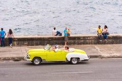 古巴,哈瓦那- 2017年5月5日:美国黄色减速火箭的敞蓬车沿Malecon沿海岸区乘坐 复制文本的空间 库存照片