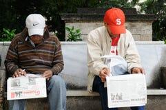 古巴:两个更老的人坐一家银行在一个公园在读报纸的哈瓦那 免版税库存照片