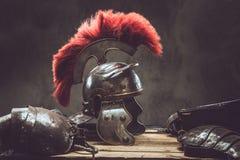 古希腊战士谎言的完全作战设备在一箱的木板 库存图片