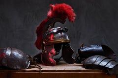 古希腊战士谎言的完全作战设备在一箱的木板 免版税库存图片