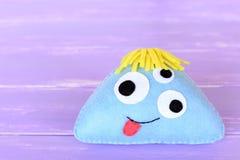 古怪的蓝色感觉在淡紫色背景隔绝的妖怪玩具 被充塞的儿童外籍人玩具 家庭织品礼物 免版税库存图片