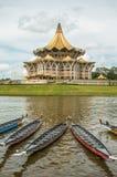 古晋、马来西亚,议会大厦和帆船附载的大艇在水节日赛船会下 免版税库存照片