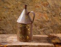 仿古有年迈的黄铜的生锈的铁瓶子在葡萄酒木头 图库摄影