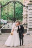 古板的哥特式门的背景的亲吻的新婚佳偶 库存照片