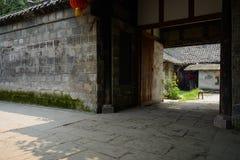 古老中国寓所门在树荫下在晴天 免版税库存图片