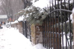 古老伪造的篱芭由金属和石头制成在冬天 免版税库存照片
