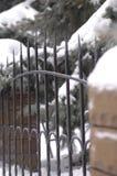 古老伪造的篱芭由金属和石头制成在冬天 图库摄影