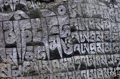 古老佛教徒雕刻了有神圣的宗教佛经的石墙 免版税库存照片