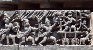古老印地安军队的战士向战斗, 12世纪Hoysaleshwara寺庙的安心求助在Halebidu,印度 库存图片