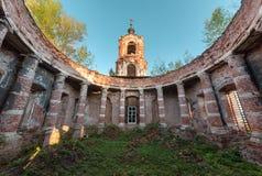 古老圆形建筑与没有一个圆顶的专栏在背景和蓝天的钟楼在日落 免版税库存图片