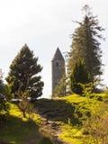 古老圆的塔在历史的Glendalough修道院站点的公墓在威克洛郡在爱尔兰 免版税库存照片