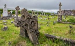 古老坟墓和墓石有鲜绿色的草的在Ballinskelligs Augustinian小修道院在凯里郡,爱尔兰 免版税图库摄影