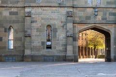 古老城堡城市墙壁 在一个石墙的被成拱形的中世纪门 发光通过石曲拱的太阳 免版税库存图片