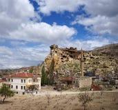 古老岩石城堡的看法在格雷梅附近的Cavusin村庄 Cappadocia,土耳其 库存图片